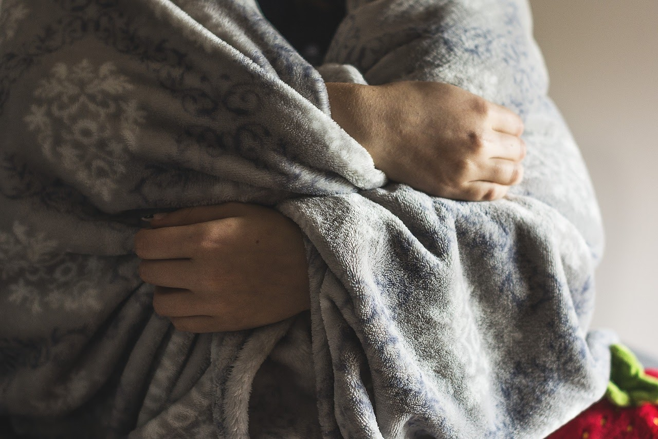 A person wraps up in a blanket appearing to be cold, another physical symptom of anxiety