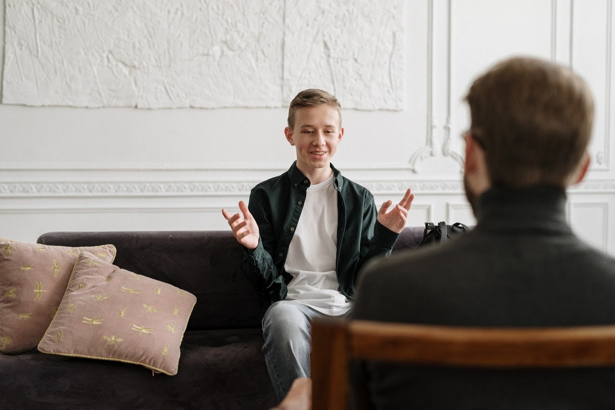 A young man appears to be having a positive conversation with his therapist.