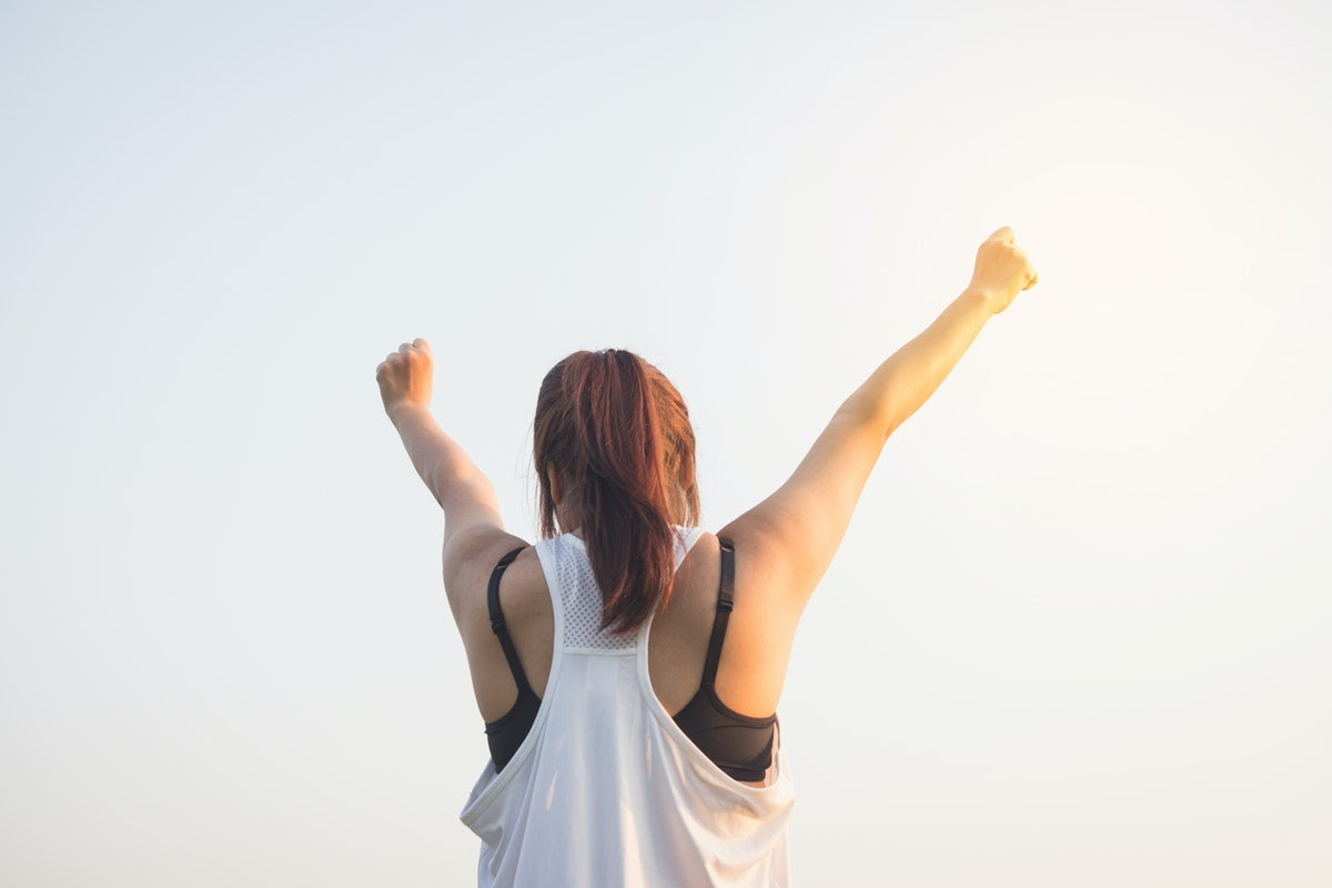 A woman stands with her arms in the air in an empowered pose.