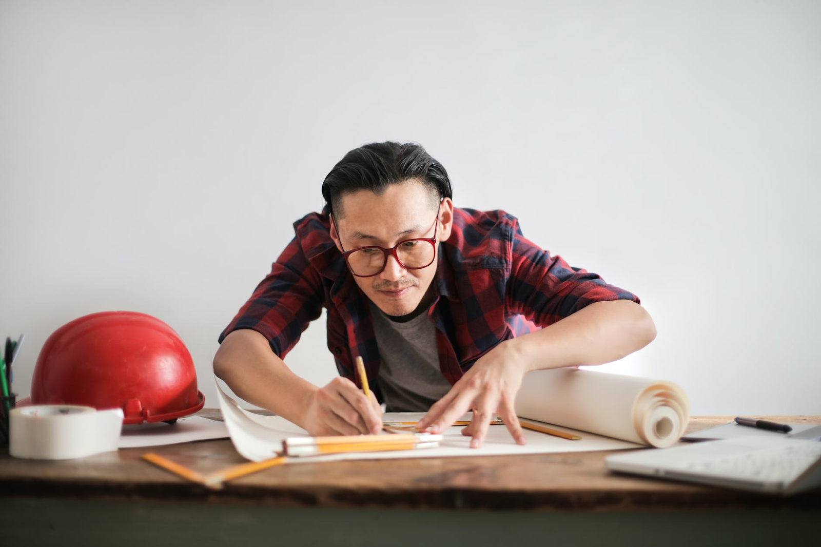 a man in a red flannel shirt who grew up as a gifted child completing blueprints for work