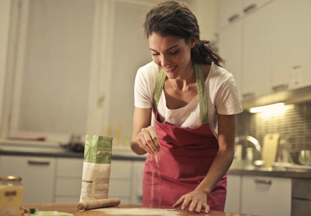 A woman smiles while sprinkling flour on kitchen counter. The woman wears an apron and loves cooking as a hobby.