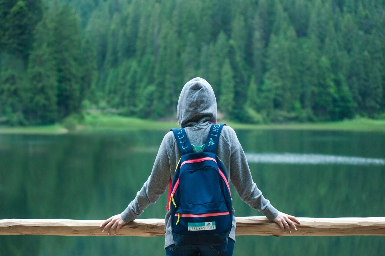 A person stands alone in a hoodie staring out at a lake surrounded by pine trees.