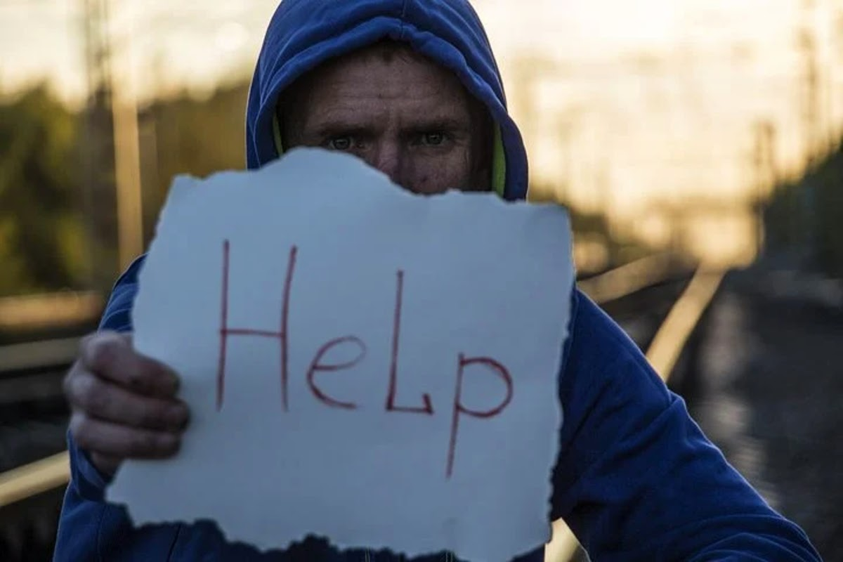 person holding up sign that says help