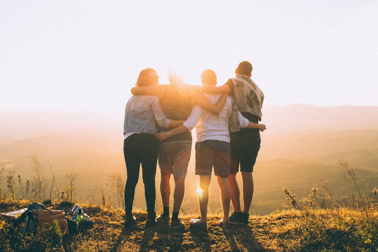 A group of four young friends hold onto each other while staring at a sunset.