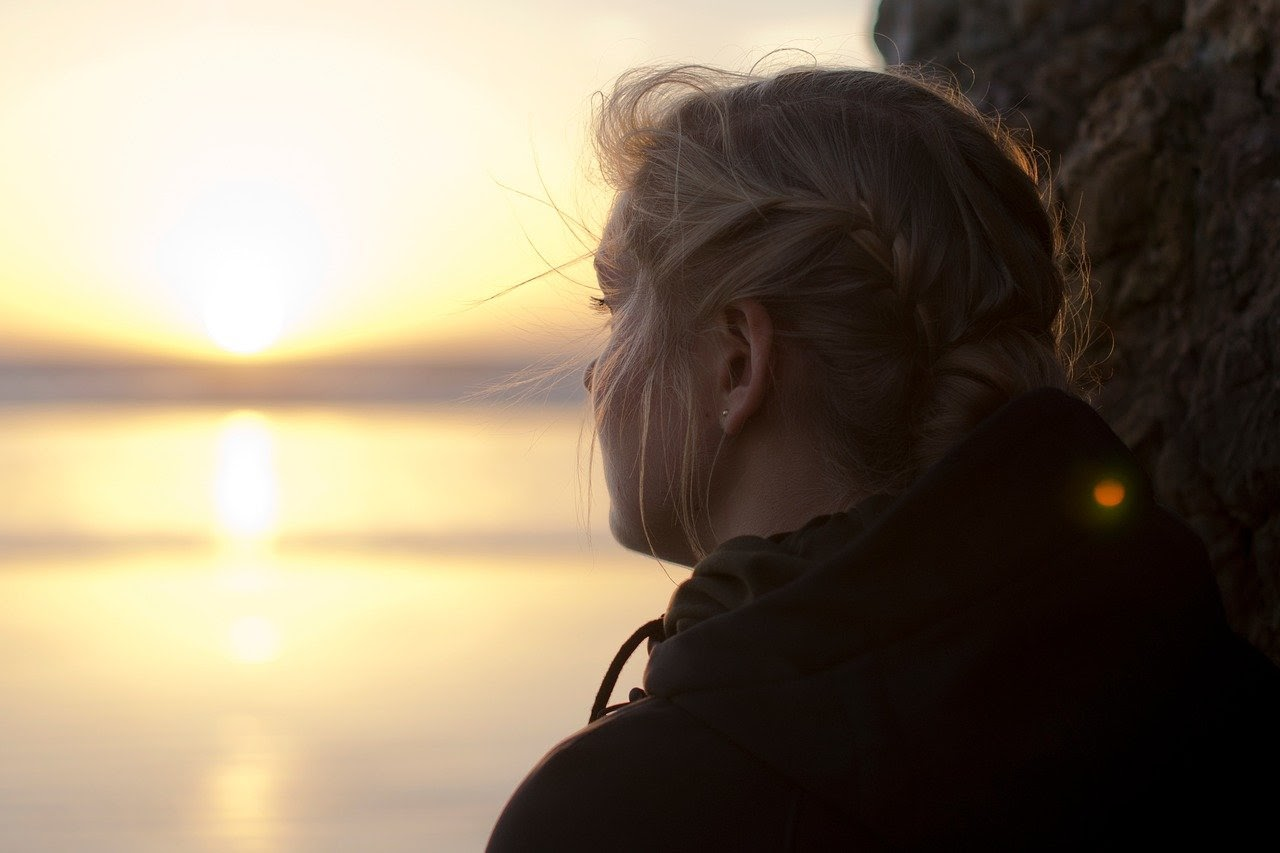 Girl looks depressed while staring out at a sunset.