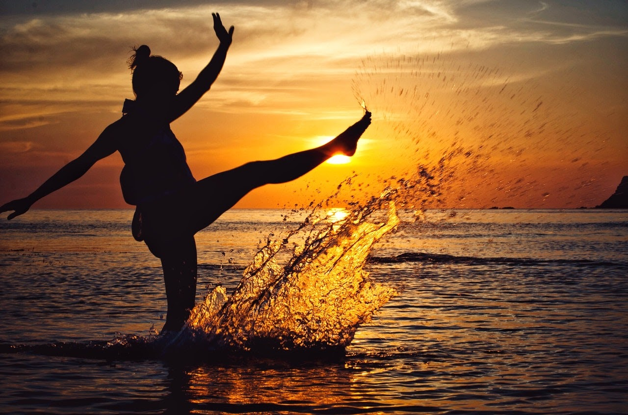 Happy woman kicking up ocean water at the beach with a sunset