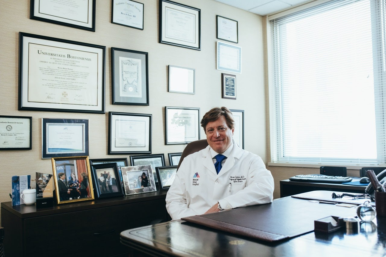 Doctor in white jacket smiles while sitting in his office
