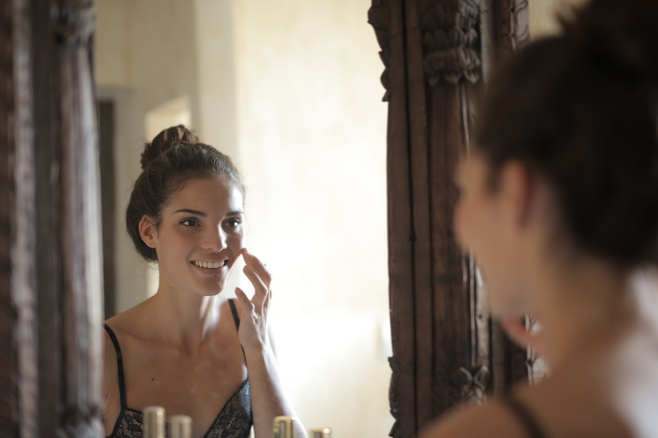 Woman smiles at her own reflection in the mirror