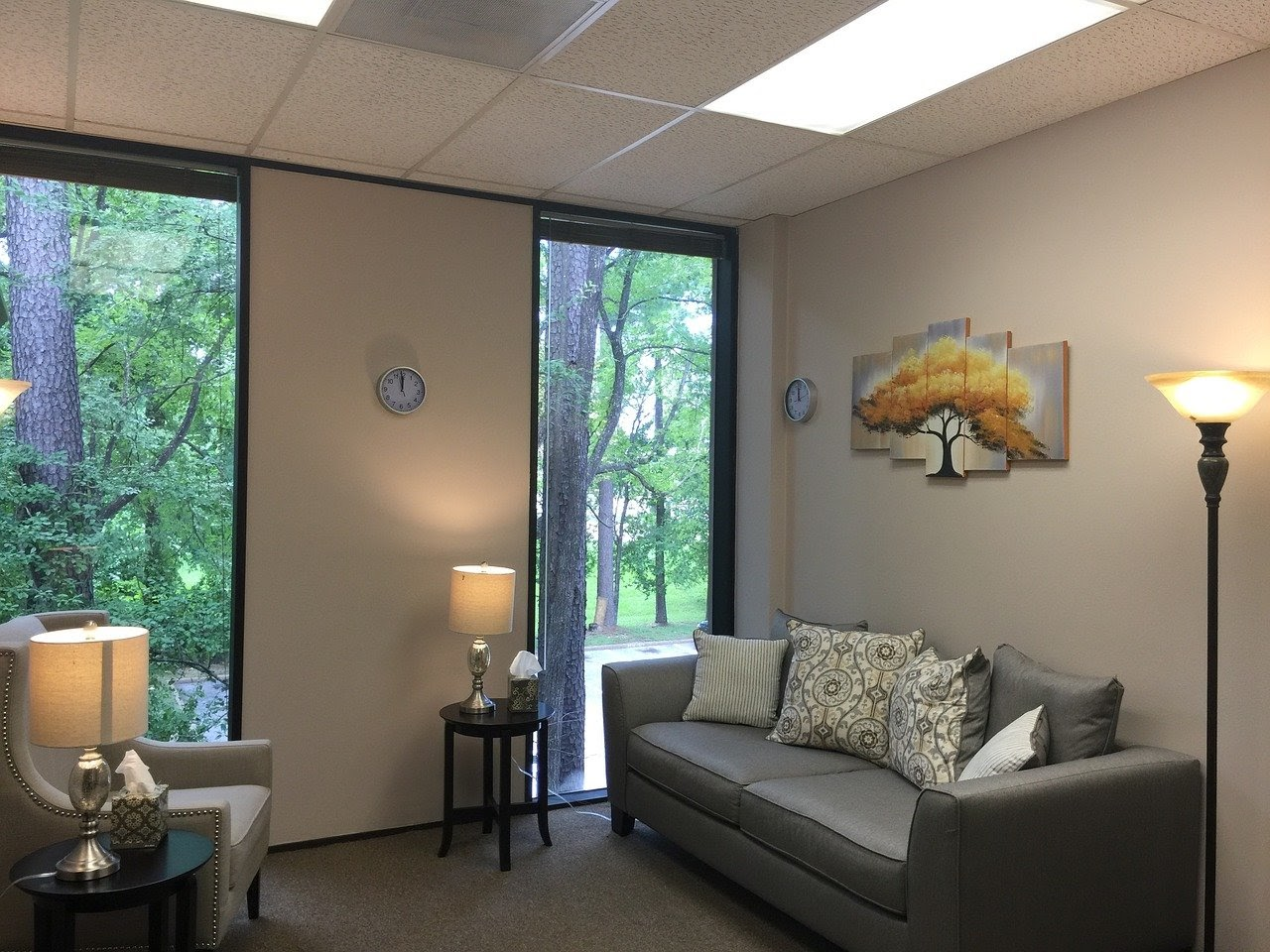 Substance abuse counselor's office with a couch, chair, and lamps lighting up the room