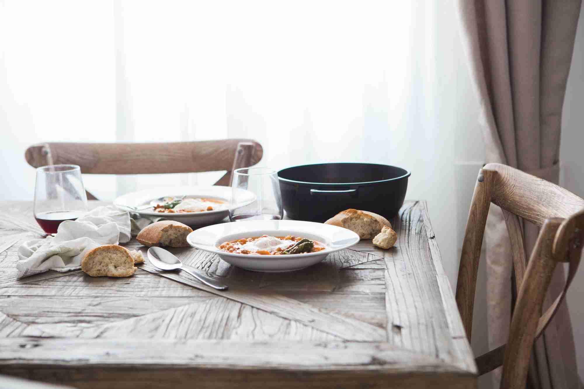 Dos platos de puchero y un par de vasos de vino encima de una mesa de madera.