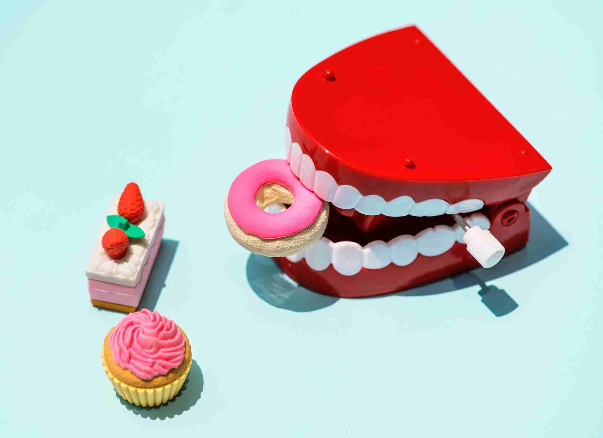 Dentadura plástica roja de juguete mordisqueando una rosquilla rosa, rodeada de una magdalena y un trozo de pastel.