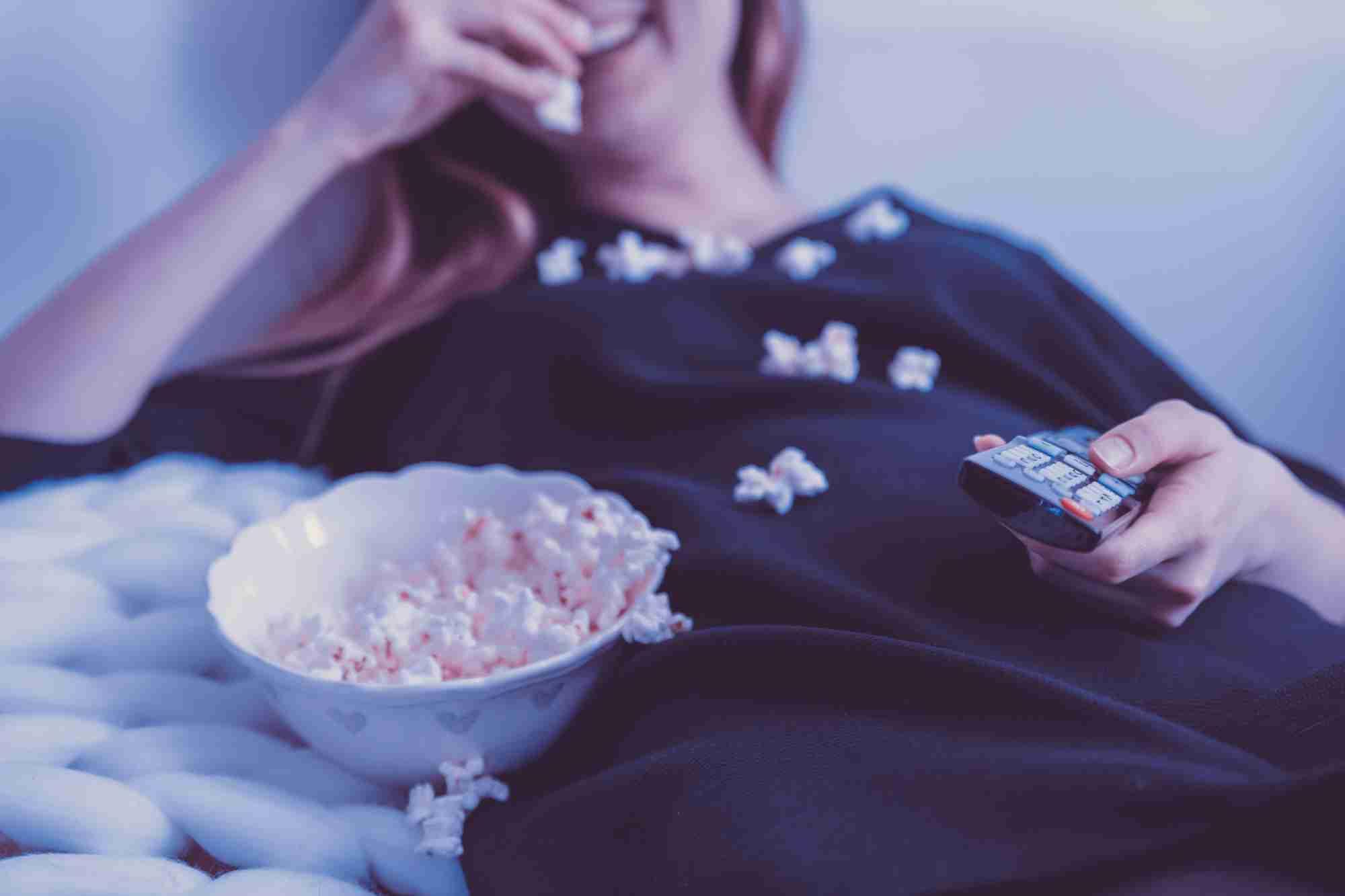 Mujer con pijama tumbada cómodamente en un sofá, con el mando de la televisión en una mano, comiendo palomitas de maíz con la otra.