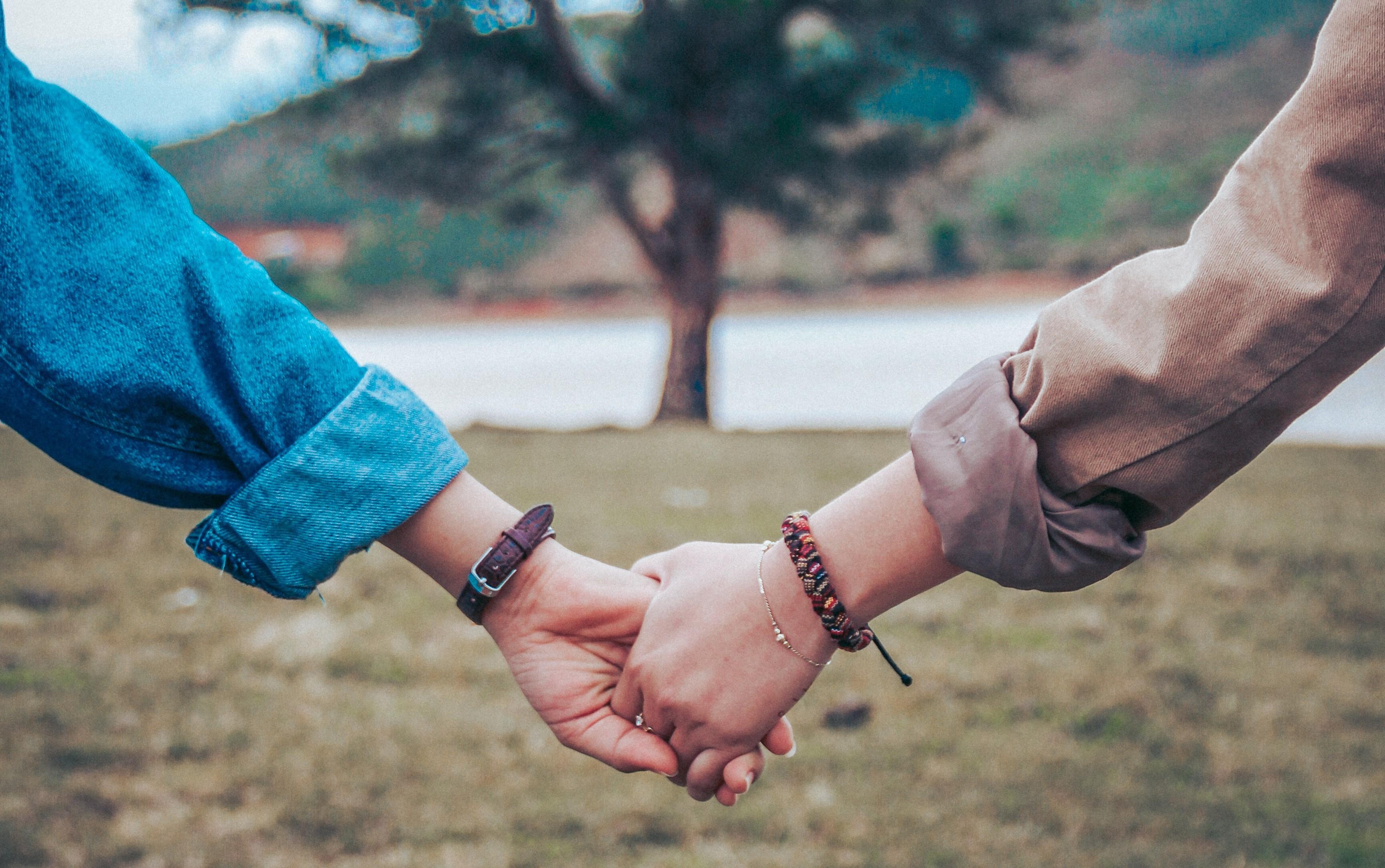 Dos personas cogidas amigablemente de la mano