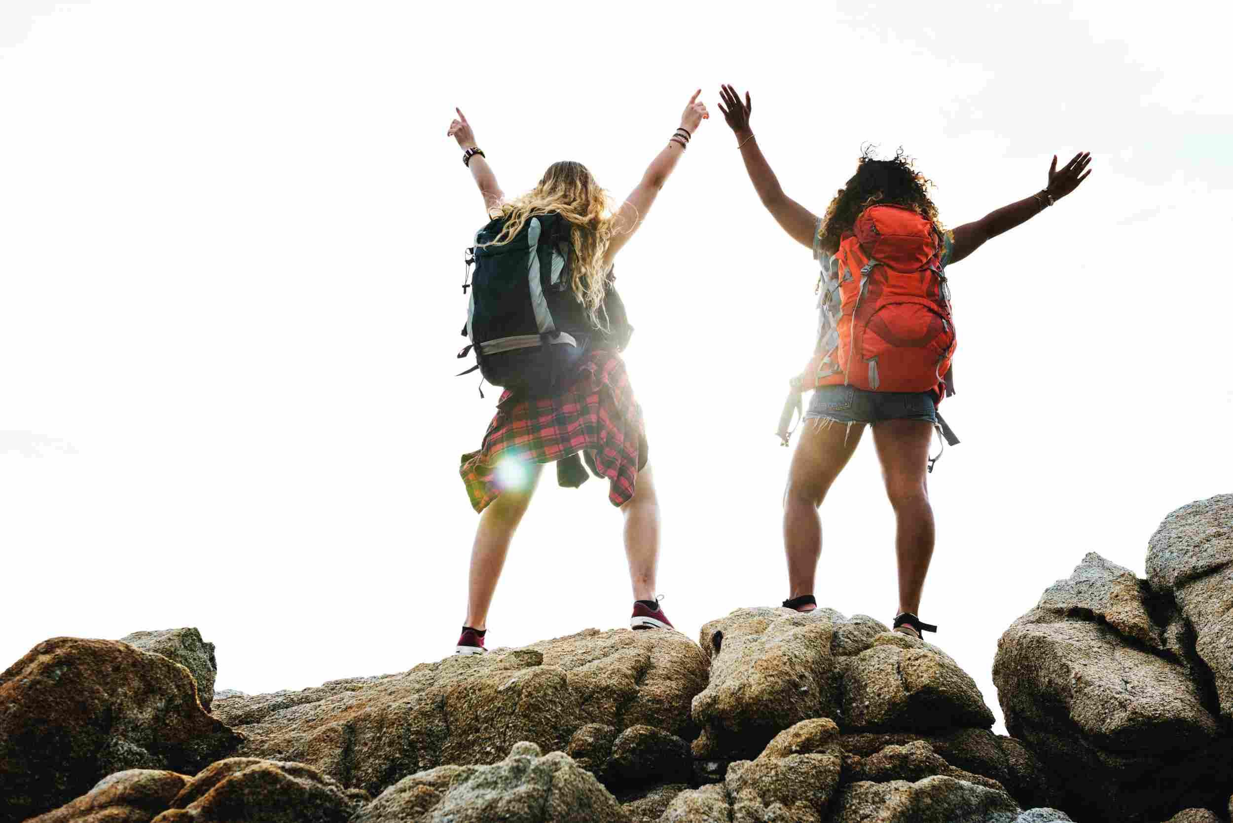 Dos mujeres están en la cima de unas rocas con ls brazos abiertos a modo de celebración.