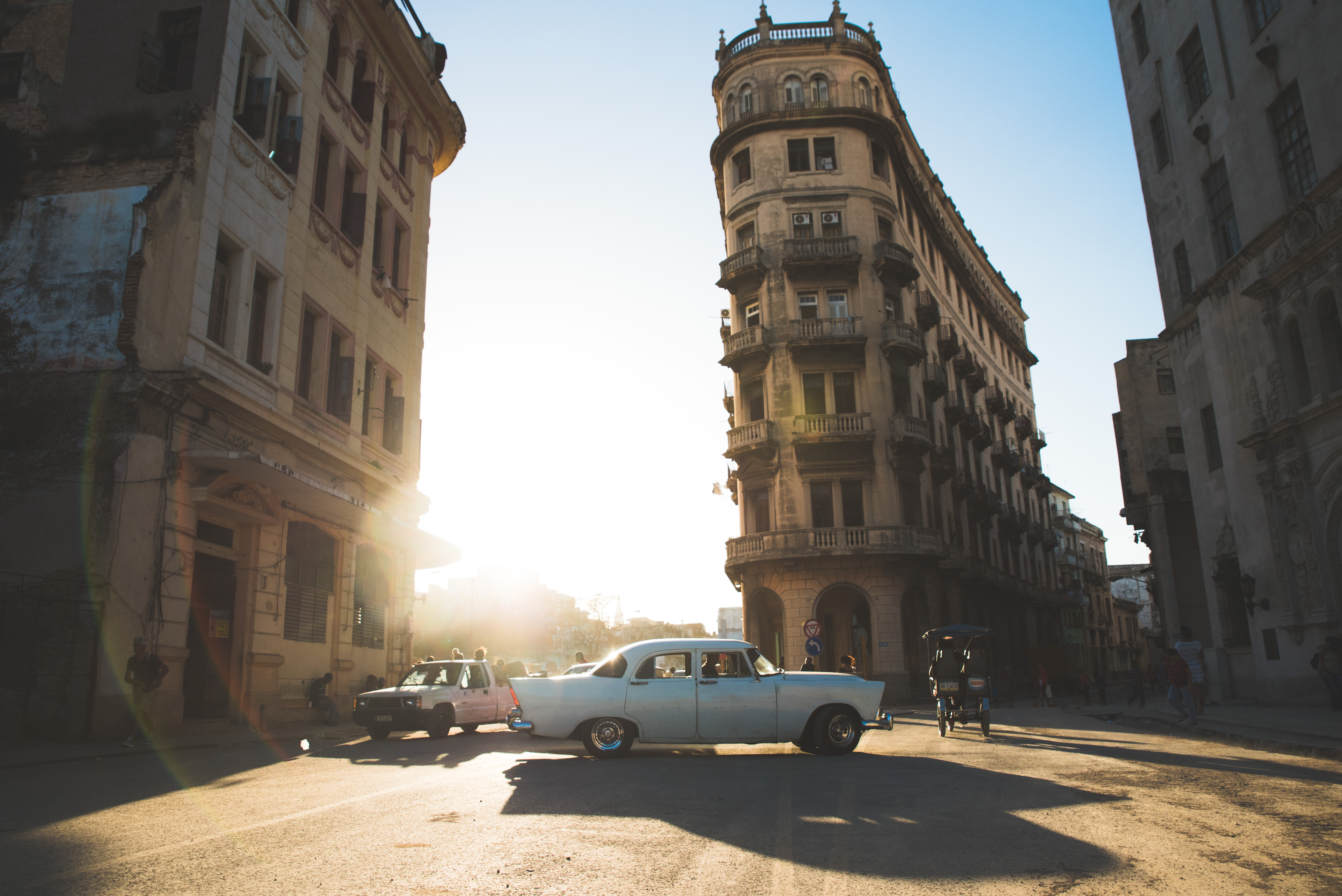 Vintage car surrounded by buildings in the sun
