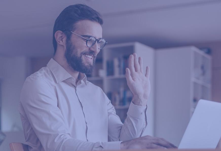 a man waving to a laptop