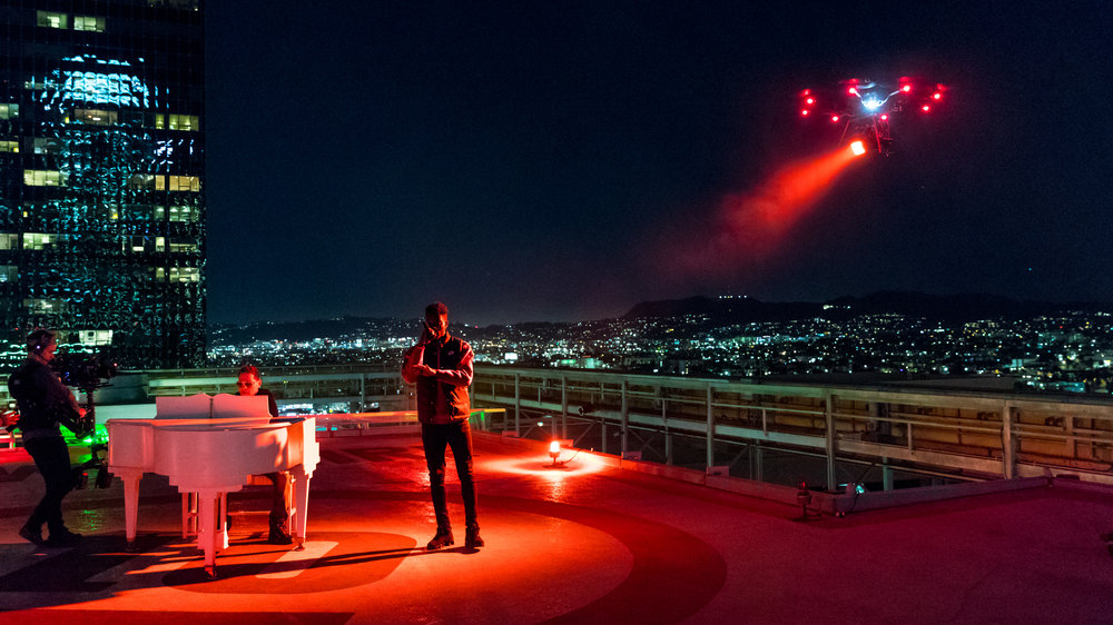 A drone lights up the helipad for Thutmose (vocals) and Storch (piano). A steadicam moves in to capture the magic of the moment.  Photo Credit: Jeffrey Moustache