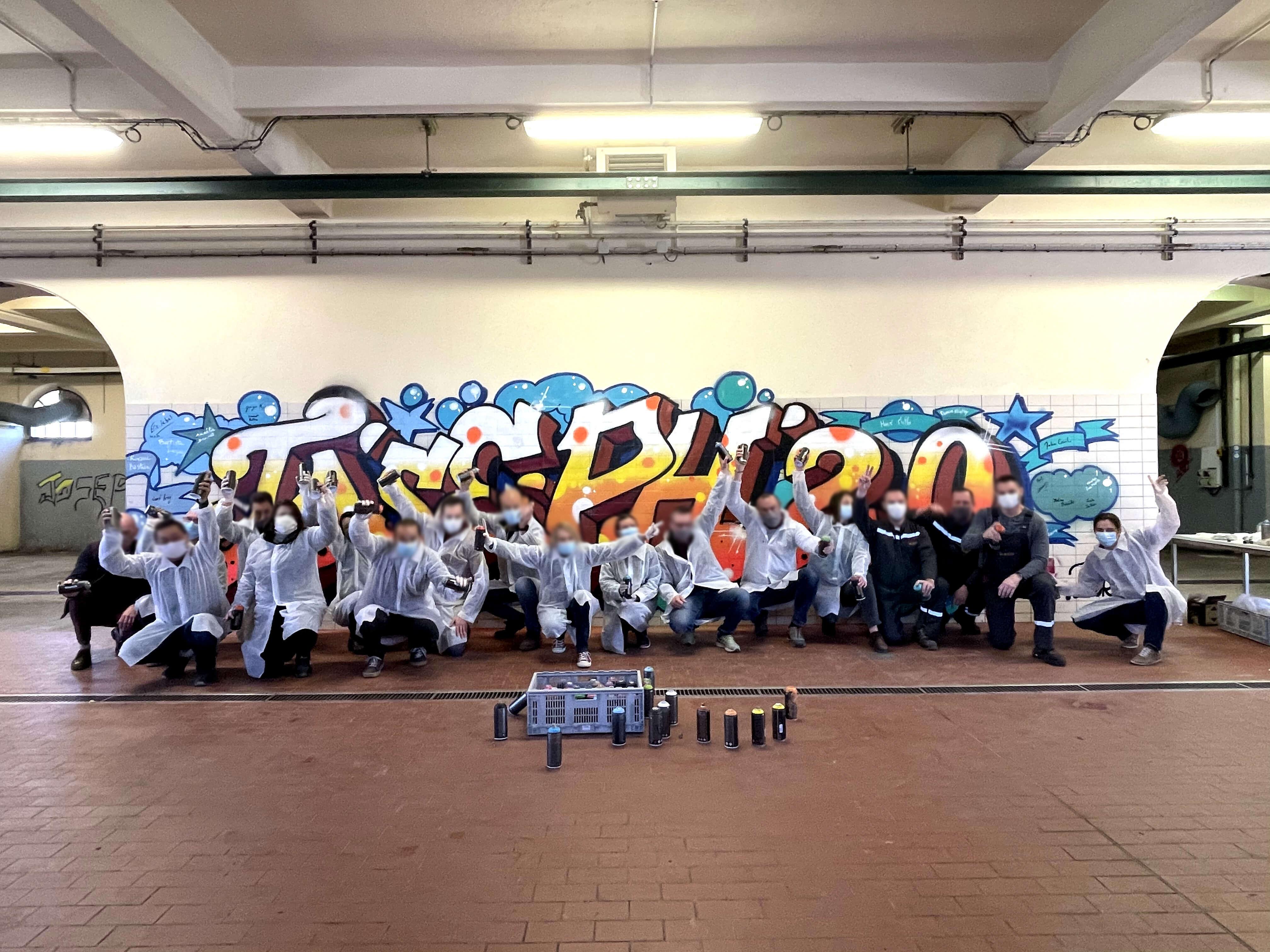 Groupe de personnes devant un graffiti