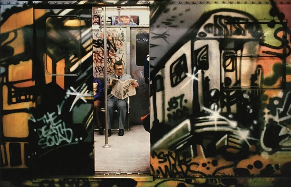 Porte de train entrouverte avec graffiti dessus
