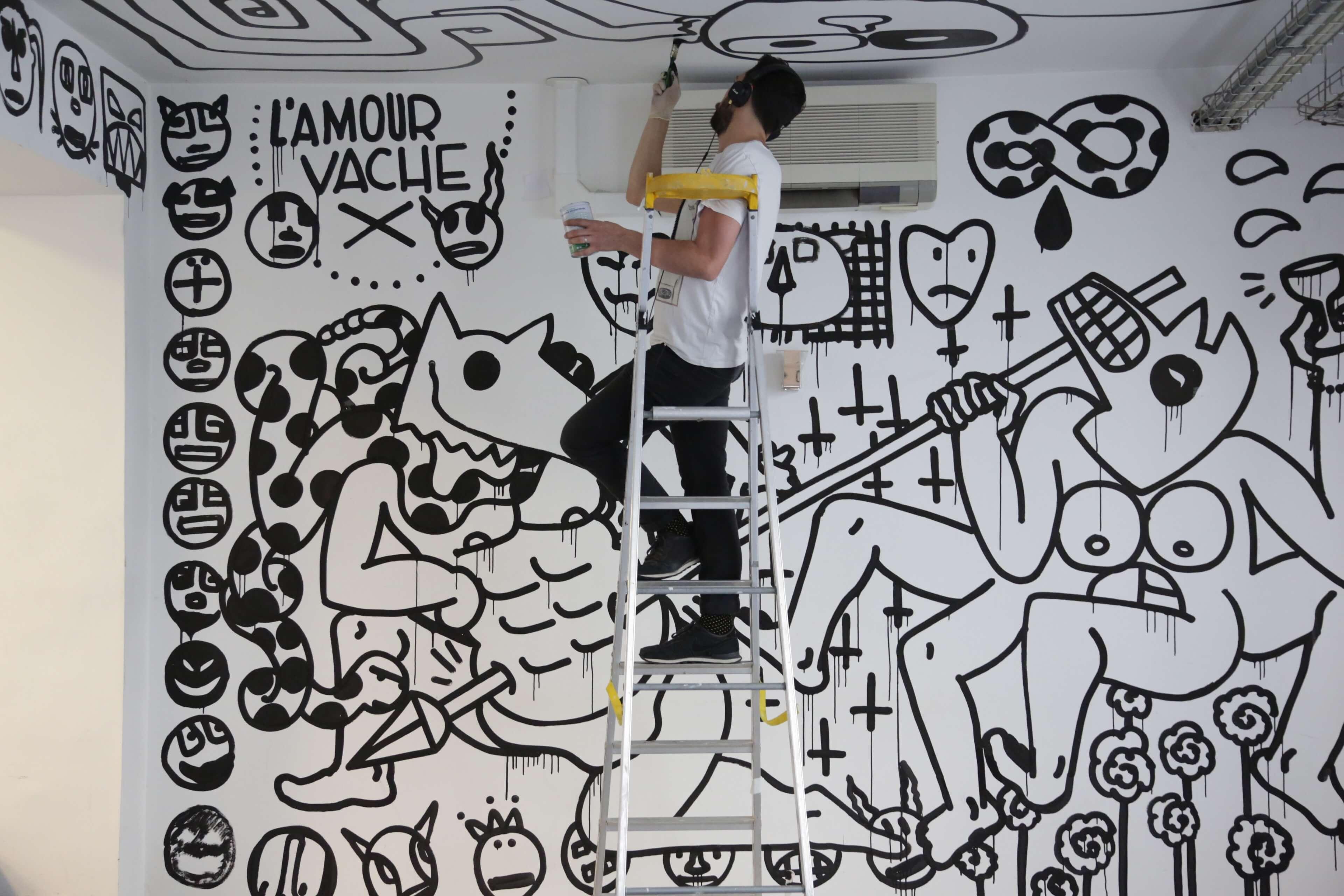 Graffeur Parisien en train de peindre le plafond de l'agence de Design Malherbe Paris
