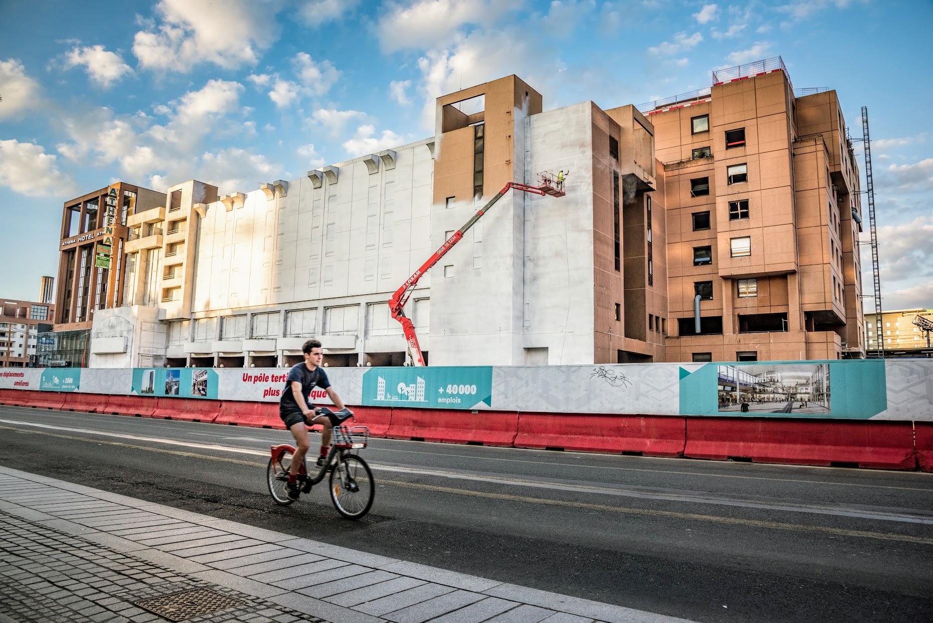 Graffeur Muraliste en train de réaliser une fresque géante sur une façade d'immeuble