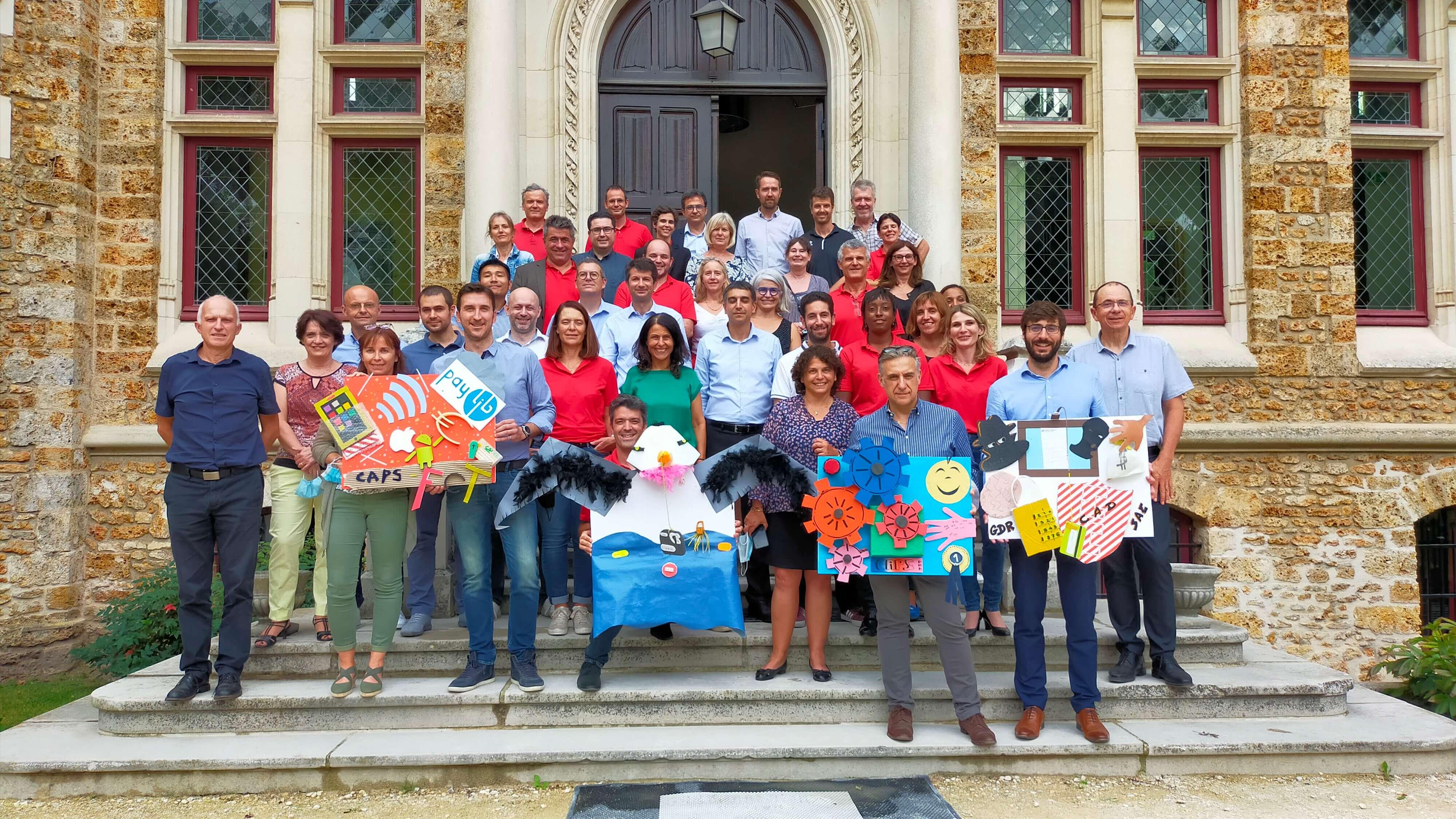 Photo de groupe avec des oeuvres issus de matériaux recyclés. team building recyclage