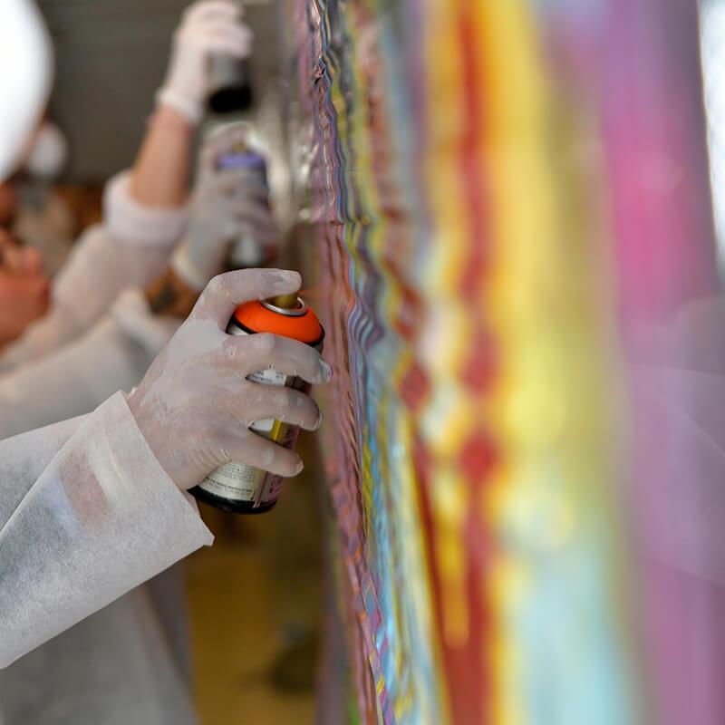 mains tenant une bombe de peinture écologique. Graffiti en team building à Paris