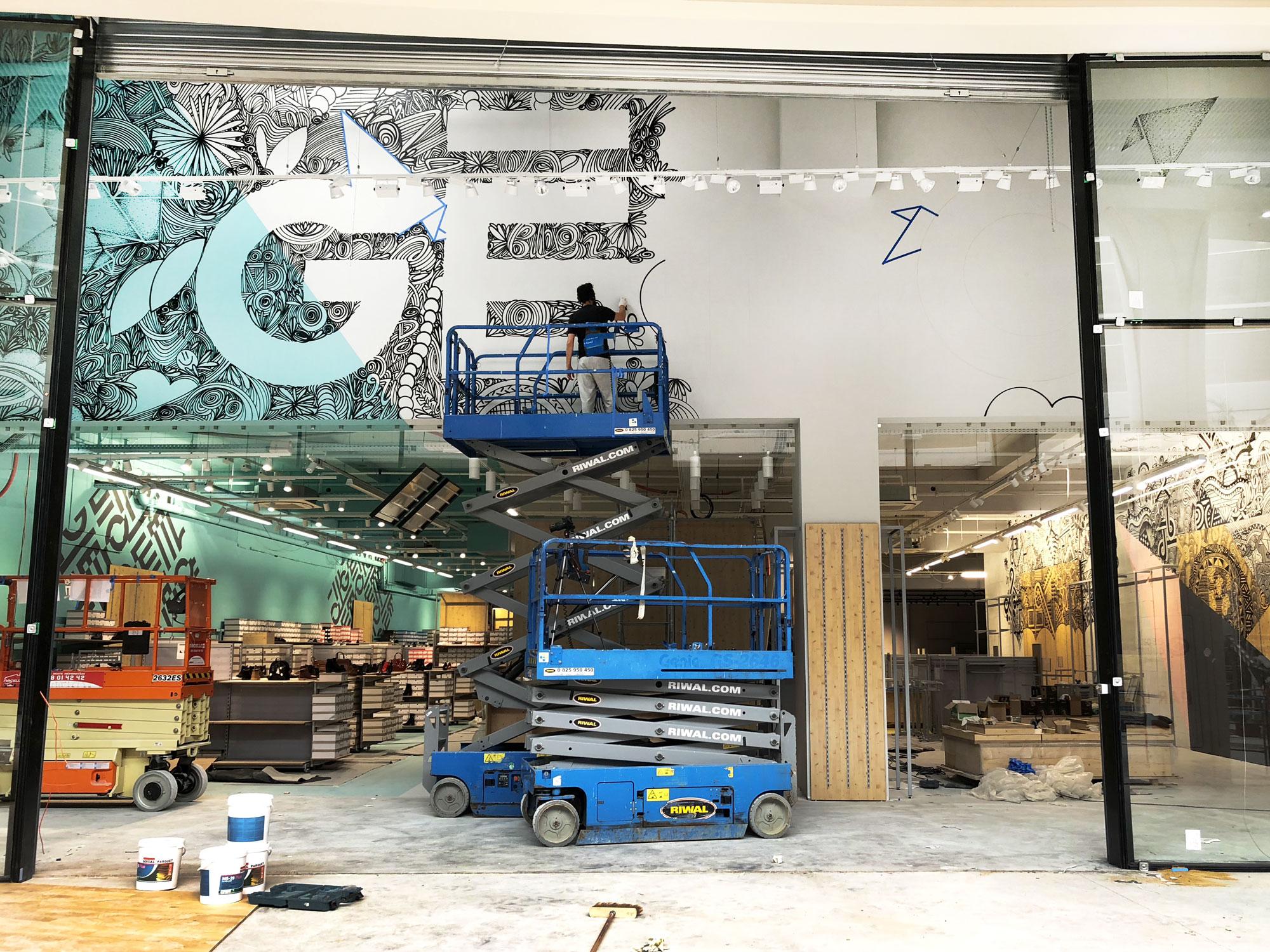 graffeur en train de réaliser une fresque géante en graffiti dans un magasin à nantes