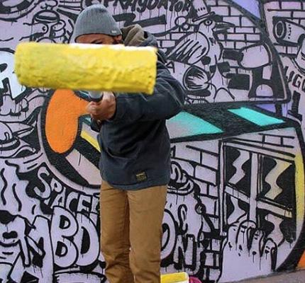 Graffeur réalisant une fresque graffiti sur un mur à Paris