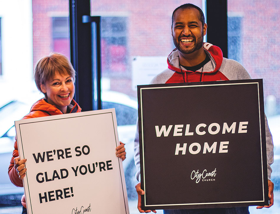 Two people holding boards that welcome people to church.