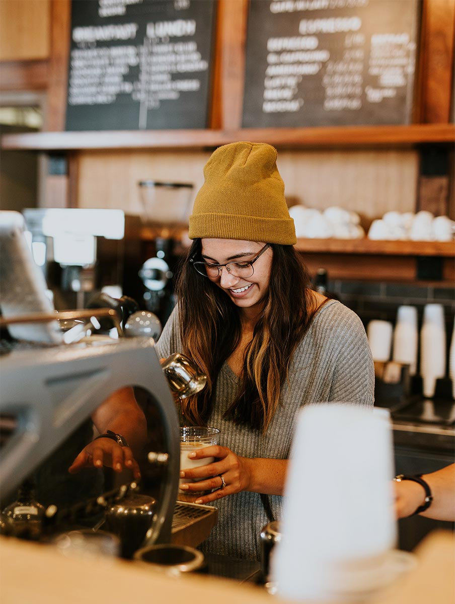 A young lady making coffee for church attendees.