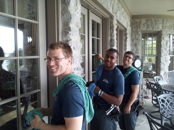 Team members of Abide Window Services smiling and looking at the camera as they clean windows.