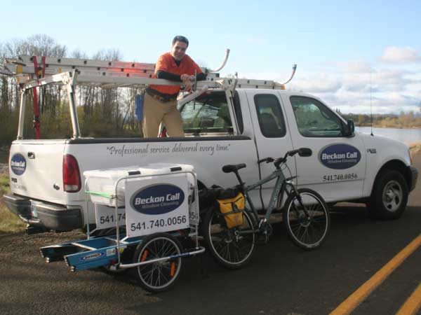 Beckon Call window cleaning truck and bicycle equipment on display with a happy team member.