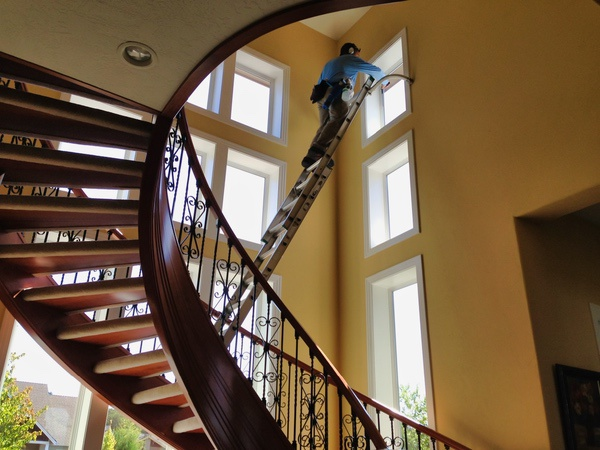 A large spiral staircase with a window cleaner on a ladder cleaning the high windows that let the natural light in.