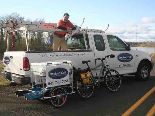A truck and bicycle with a wagon attached that displays the logo of Beckon Call window cleaning being advertised.