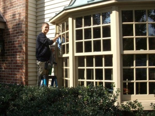 The bay window of a home in Yardley Pennsylvania being washed by a happy team member of Clear View Window Cleaning.