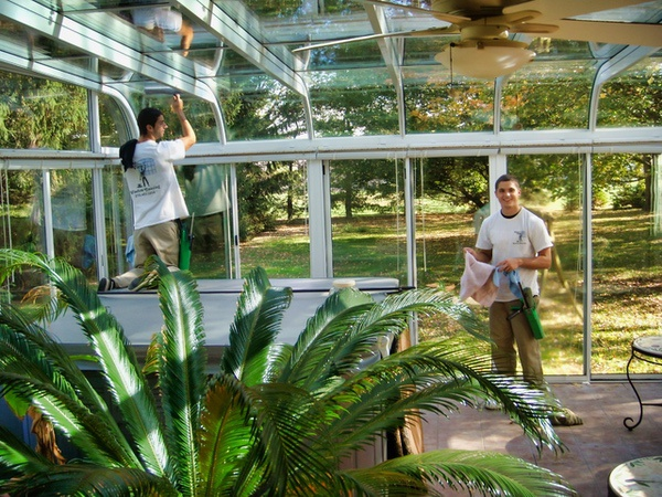 Professional Window Cleaners wash the windows of an all glass solarium as the sun shines in.