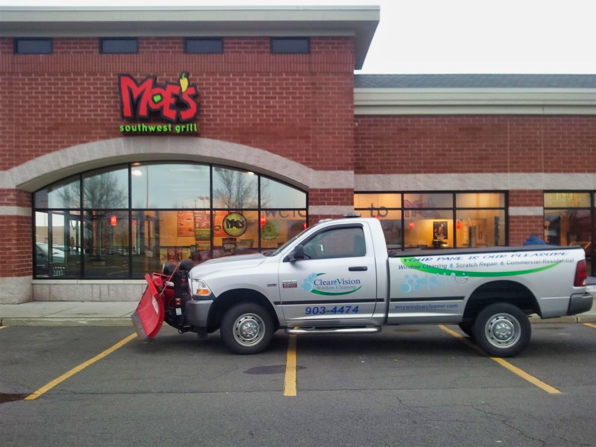 A truck with the logo Clear Vision Window Cleaning displayed on the side parked in front of a business with clean windows.