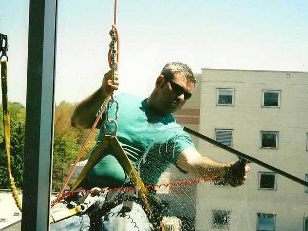 Window cleaner that is being suspended by a rope doing window cleaning in Rehoboth Beach Delaware.