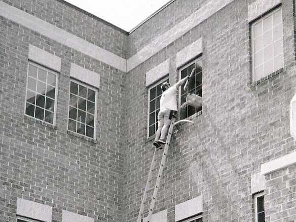 Third Floor windows of a brick building being cleaned by a team member from Clear View Window Cleaning.