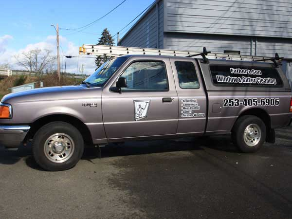 A truck with the logo Father and Son Window Cleaning displayed on the door and side back window in Gig Harbor.