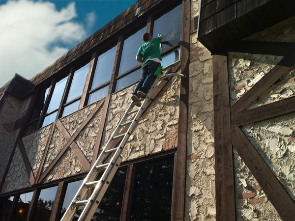 A team member from Lions Share Maintenance on a ladder cleaning windows.