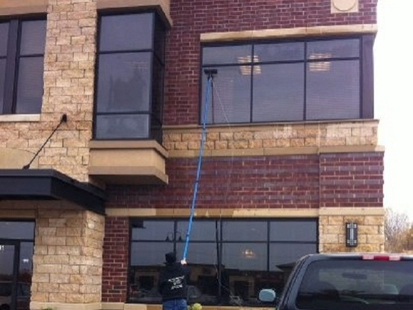 Exterior commercial window washing being done to the second story of a building from the ground with a long pole.