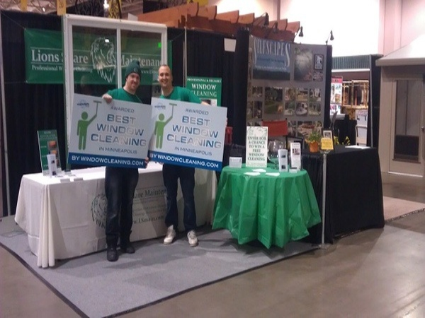 Lions Share Maintenance team members smiling and holding up Best Window Cleaning award at a trade show.
