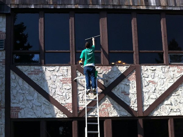 Window washing being done by team member on a ladder in Minneapolis Minnesota.