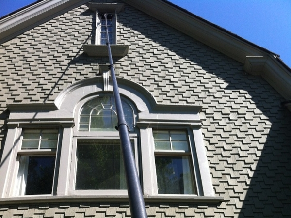 Window Washing being done on a window at the peak of a house in Woodbury Minnesota.