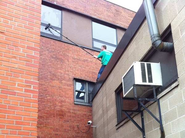Apartment windows being cleaned with a window cleaning pole in Saint Paul.