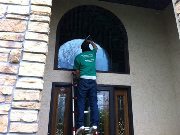 A team member cleans the windows of the front entrance of a residence in Minnesota.