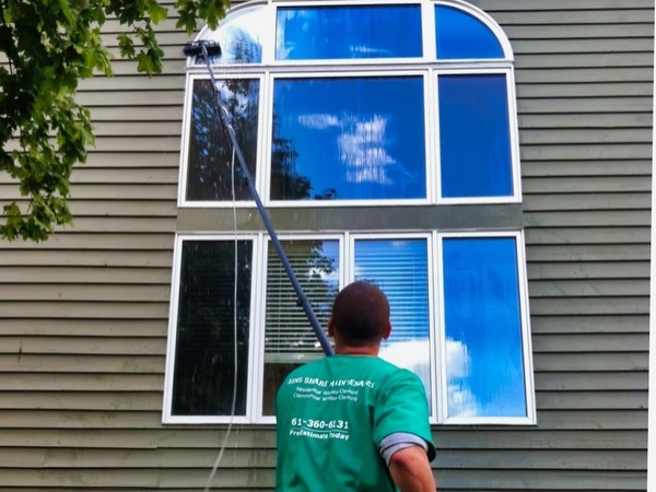 A home window being cleaned by a man with a water fed pole in Woodbury Minnesota.
