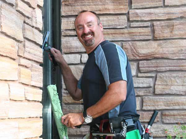 Smiling window washer looks straight on at the camera as he is working in Kalispell.